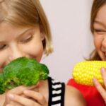 Children holding and eating vegetables