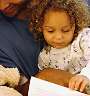 man reading with child at bedtime