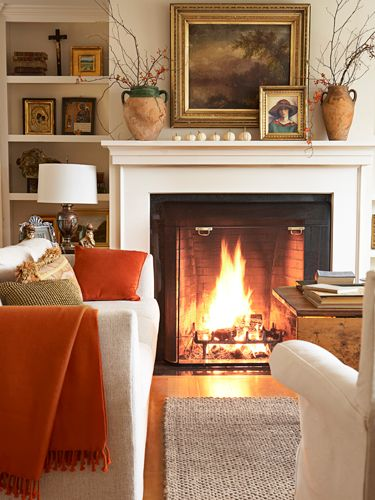 A fire warms a cosy room with a comfortable sofa