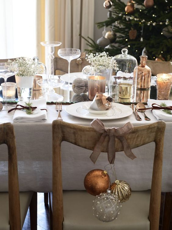 Table decorated for Christmas dinner with a Christmas tree in the corner