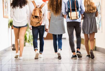 Four teenagers walking down a school hallway with rucksacks on their back.