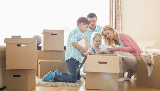 A family kneel on a wooden floor to unpack brown moving boxes.
