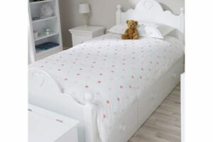 White wooden child's bed with white bedding complete with love hearts dotted all over. A teddy sits on top of the bed.